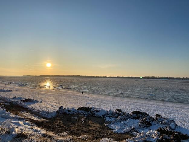 Закат на берегу замерзшей волги. лучи солнца отражаются на льду. вдалеке виднеется силуэт мужчины. горизонтальная ориентация