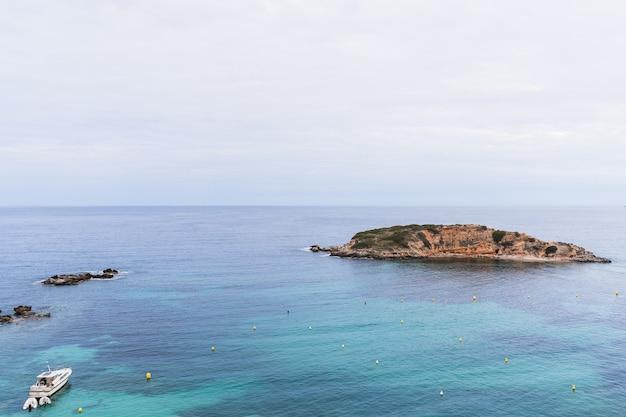 스페인 팔마 데 마요르카(palma de mallorca) 앞에 섬이 있는 푸에르토 포르탈스(puerto portals) 해변에서 일몰