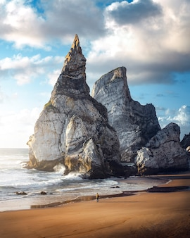 ポルトガルの海岸の岩の間を散歩している男とシントラのウルサのビーチに沈む夕日