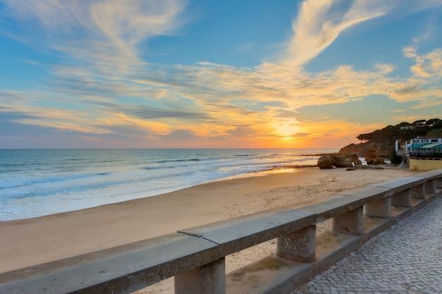 Закат на пляже ольюш-де-агуа. португалия албуфейра.