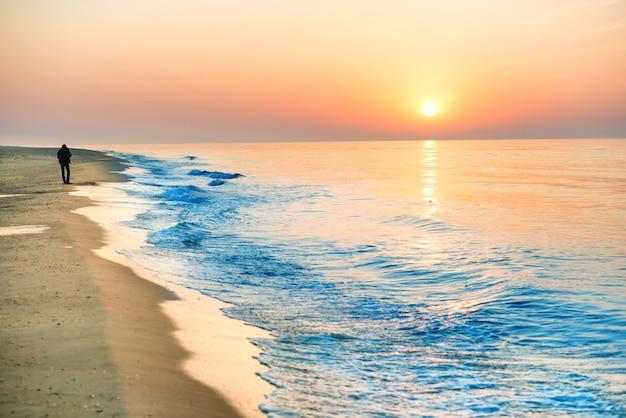 긴 해안선과 남자 실루엣이 있는 해변의 일몰, 태양과 극적인 하늘
