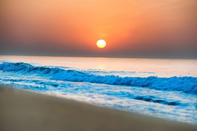 긴 해안선, 태양 및 극적인 하늘이 있는 해변의 일몰