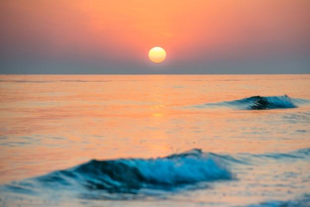 Закат на пляже с длинной береговой линией, солнцем и драматическим небом