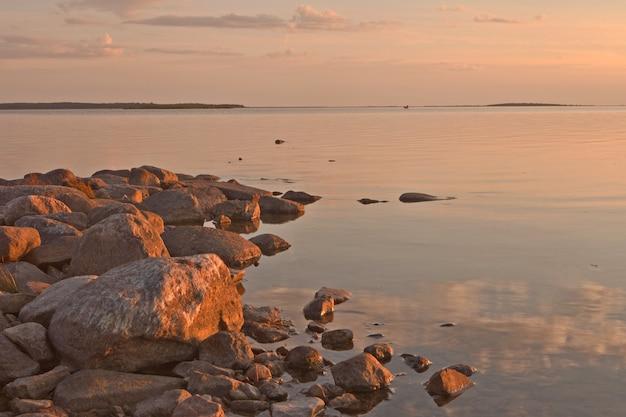 穏やかな海とピンクの空と岩のあるハープサル市のエストニアのバルト海沿岸の夕日