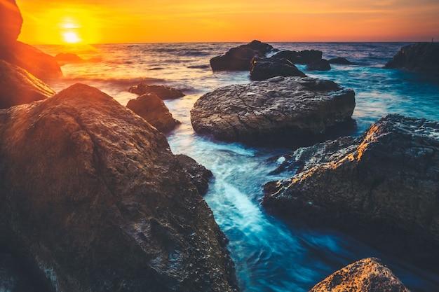 夜明けにスリランカの海岸に沈む夕日。前景に岩があります。美容の世界