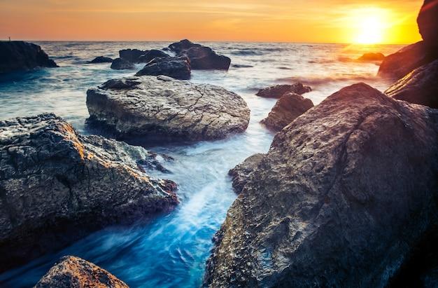 前景の美しさの世界の岩と夜明けにスリランカの海岸に沈む夕日