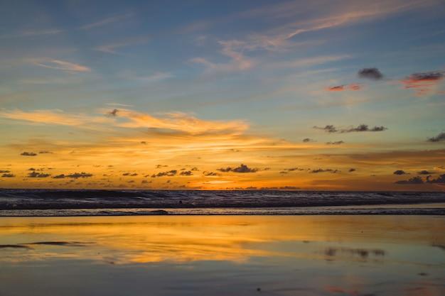 Закат на океан. красивое яркое небо, отражение в воде, волны.