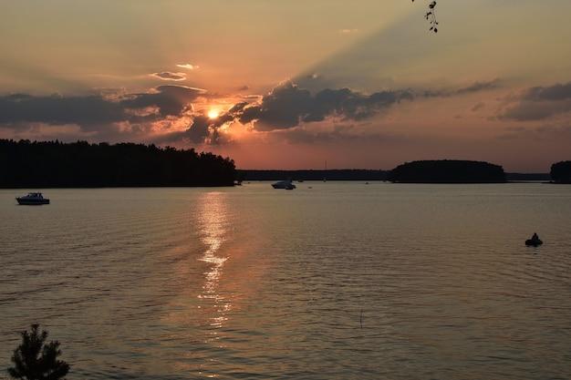 貯水池の夕日、湖の夕日、夕日の背景に漁師のシルエット