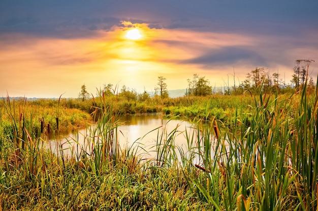 川に沈む夕日。日没時に川と絵のように美しい空と秋の風景