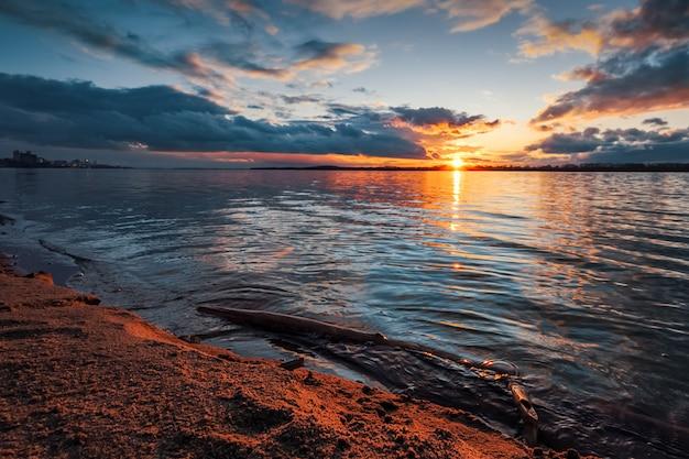 Закат на берегу реки. красивые облака, голубая газированная вода, упавшая ветка дерева в воде и песок на берегу оранжевого цвета от лучей заката.