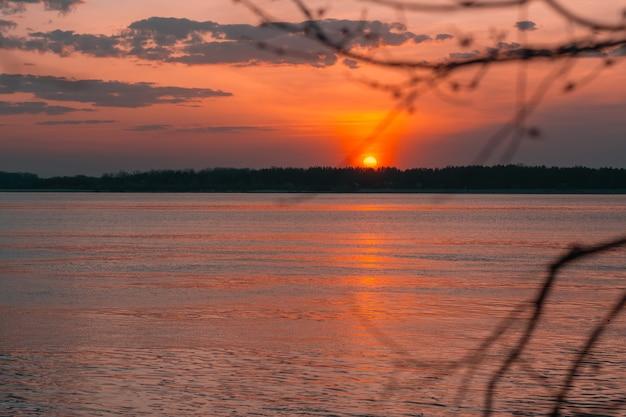 Закат на реке летним вечером. спокойная вода в оранжевых лучах солнца.