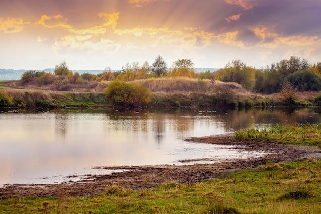 川に沈む夕日。絵のように美しい秋の風景