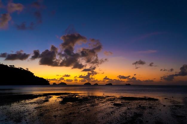 Закат на тропическом пляже. оранжевый закат на берегу океана. красочный закат в тропиках