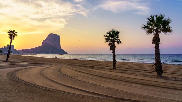 ヤシの木と海の大きな岩のある白い砂浜に沈む夕日。カルペアリカンテ。