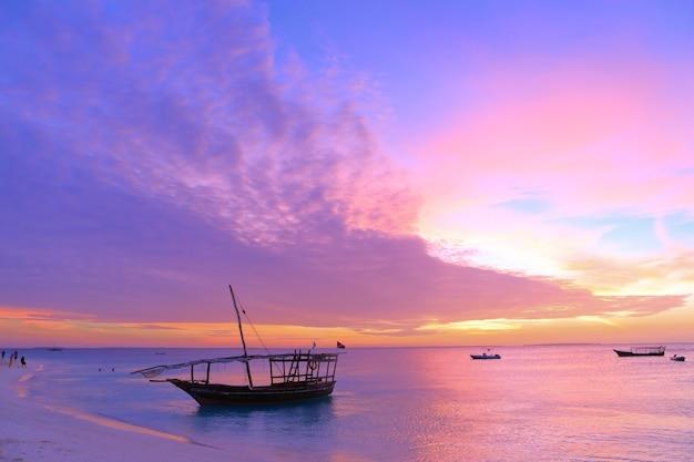 Закат на занзибаре в аутентичной африканской деревянной лодке на живописном берегу океана