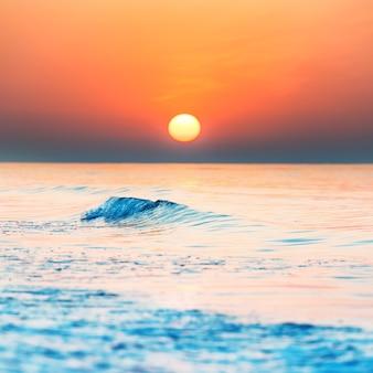 美しい劇的な空に太陽と海に沈む夕日や日の出