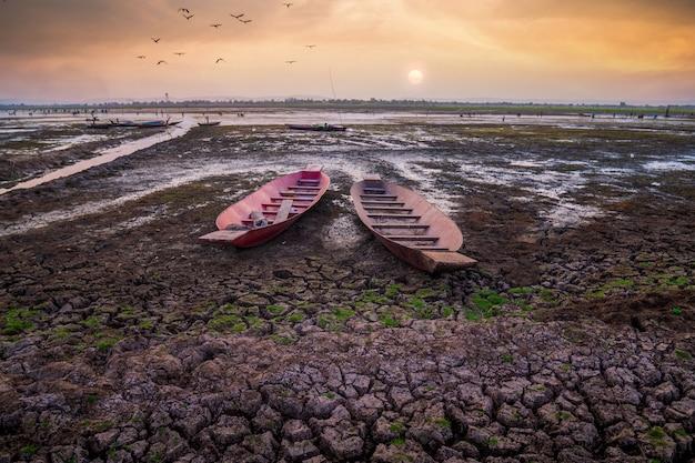 건조한 땅과 어선이 있는 일몰 또는 일출