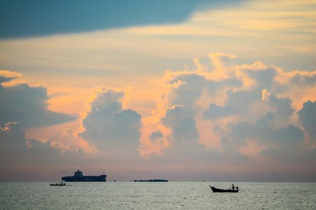 Закат оранжевого облака обратно на темном небе силуэта и рыбацкой лодке на море