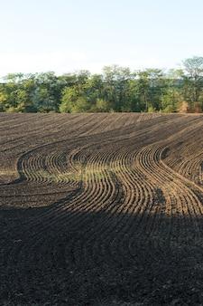Закат над вспаханным полем с коричневой почвой. красивый осенний пейзаж.