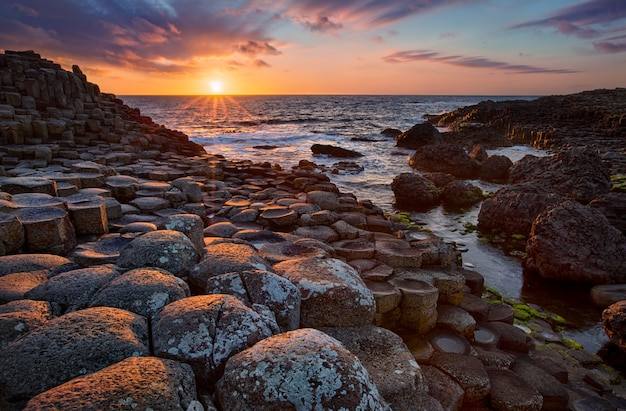 玄武岩の柱に沈む夕日ジャイアンツコーズウェイ、アントリム州、北アイルランド