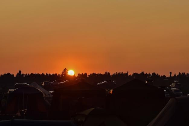 キャンプ場に沈む夕日、オレンジ色の夕日、オレンジ色の空