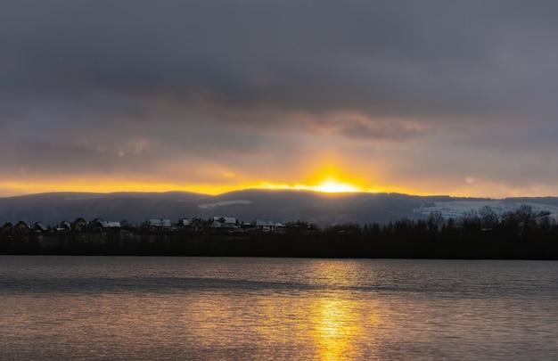 山の湖に沈む夕日冬のズデーテン山地