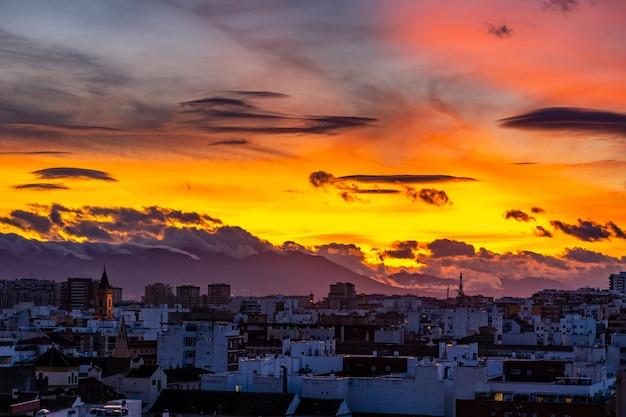 スペイン、マラガに沈む夕日-部分的に曇り、黄色と赤の空
