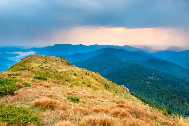 Закат над горами и холмами с сухой желтой травой