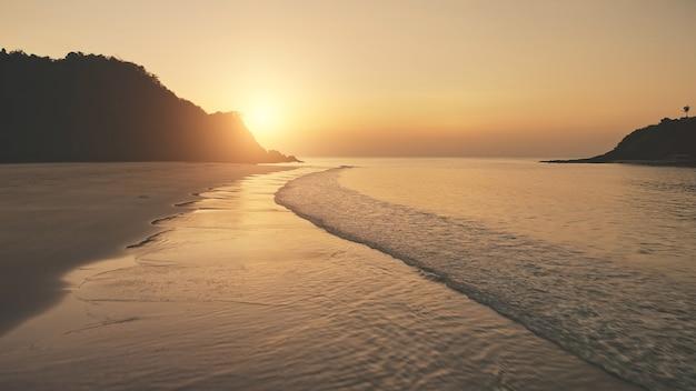 파도 위에 일몰 모래 해변을 씻어. 공중 태양 산 실루엣 위에 설정합니다. 트로픽 아무도