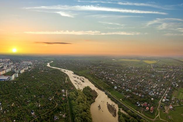 Закат над сельской местностью в городе с широкой рекой и желтым солнцем.