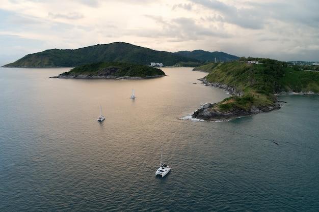 美しい夕日の空を見るために観光船のヨットで海に沈むレムプロムテップ岬プーケットタイの風景自然の景色、プーケットビューポイントはタイの有名な観光地です。