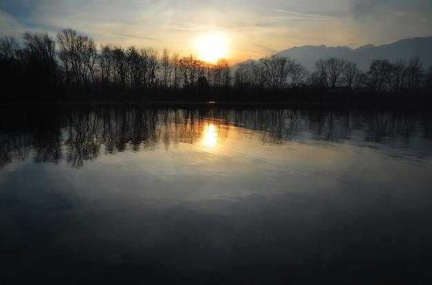 夕方には木々やスイスアルプスに囲まれた高山湖に沈む夕日