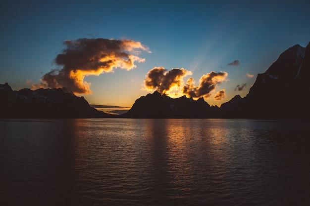 Закат над горами у моря. силуэт гор. красивые облака.