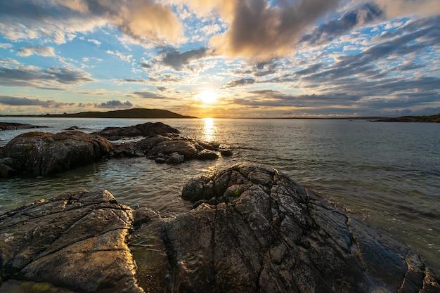 Закат над горизонтом океана теплым летним вечером возле небесной дороги в коннемаре.