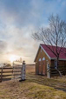 アイスランドの歴史的なkalfafellsstadur教会のための離れ家に沈む夕日