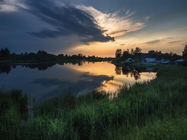 川と背の高い草に沈む夕日