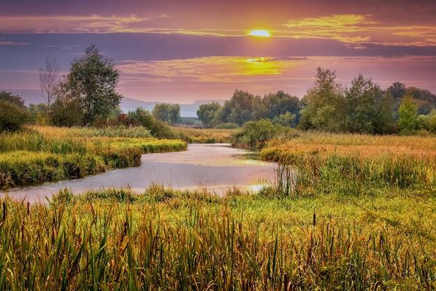 川に沈む夕日。夕暮れ時の川と色とりどりの雲と絵のように美しい秋の風景。