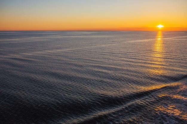 海に沈む夕日。青い水の背景。自然な壁紙。活気に満ちた風景。晴れた日の水の質感。海の表面。海に小さな波紋。美しいオレンジ色の夏の夕日