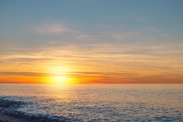 Закат над морским горизонтом. солнце заходит в море. в конце дня пора отдохнуть и расслабиться.
