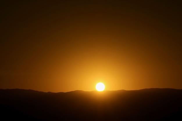 アタカマ砂漠のチルの月の谷から見た山脈のシルエットに沈む夕日