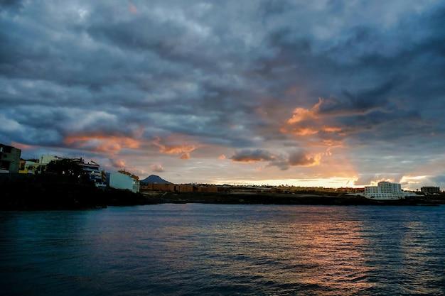 スペイン、カナリア諸島の曇り空の下で水に沈む夕日