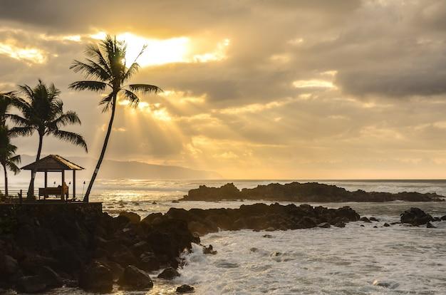 Закат над волнами, омывающими скалы в парке апперс бич на северном берегу оаху в