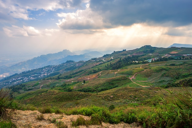 Sunset of panoramic view mountain range with village on nature trail in phu thap buek national park in phetchabun, thailand.