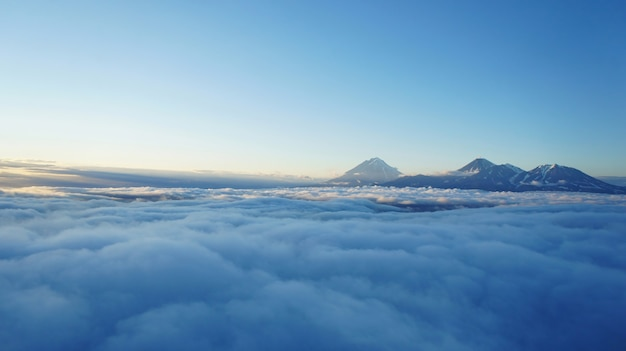 Sunset photo of kamchatka volcanoes. high altitude above clouds. shadows over cloud layer and mountains