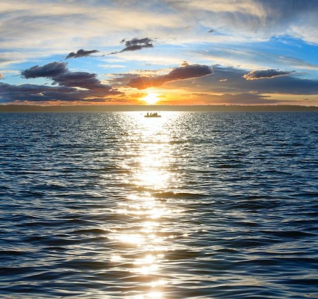 Живописное небо заката, солнечная дорожка и рыбацкая лодка на поверхности летнего озера. люди неузнаваемы.