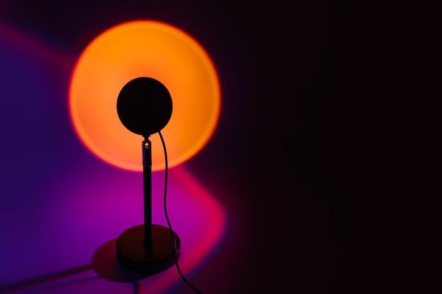 어두운 배경에 노란색 빛이 있는 일몰 프로젝터 램프.