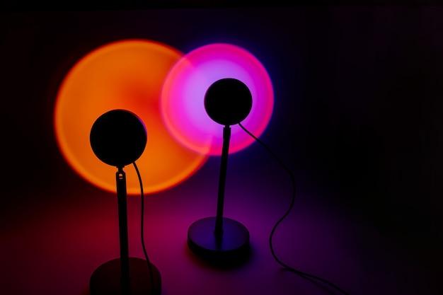 어두운 배경에 노란색과 분홍색 빛이 있는 일몰 프로젝터 램프.