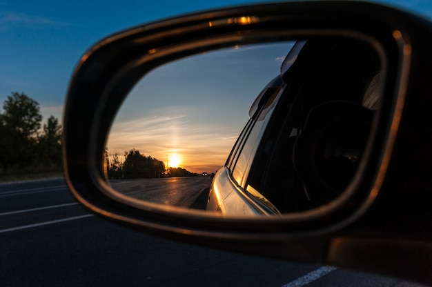 Sunset in the rear view mirror of a car