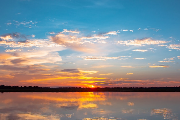 Sunset reflection lagoon. beautiful sunset behind the clouds and blue sky above the over lagoon landscape. dramatic sky with cloud at sunset