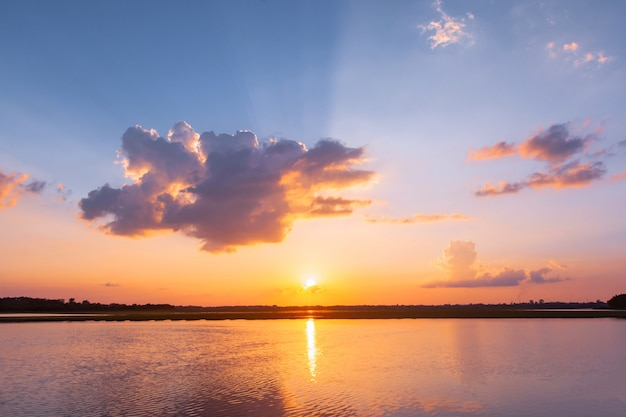 Sunset reflection lagoon. beautiful sunset behind the clouds and blue sky above the over lagoon landscape